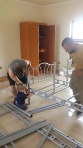 Daddy and son putting together 1 of 20 beds